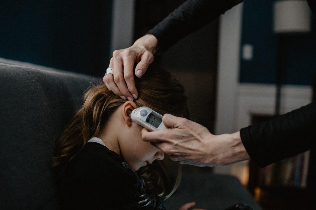 Mulher medindo febre de criança com termômetro digital